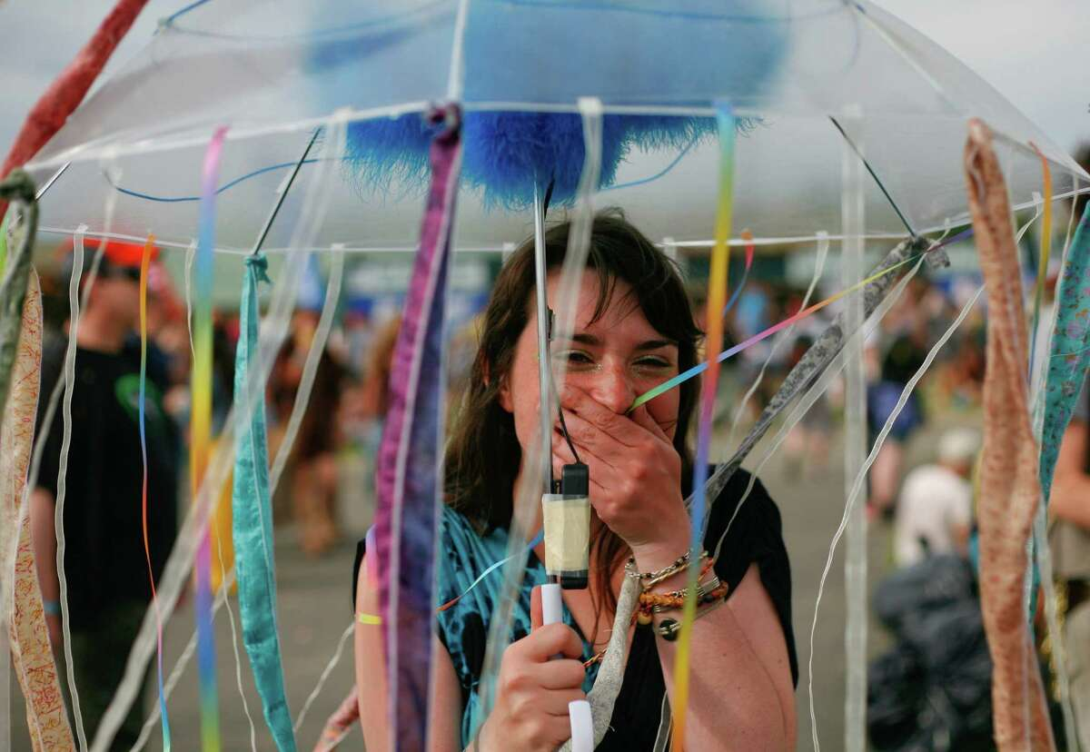 A concert attendee shows off her decorated umbrella.