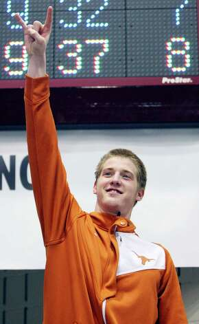 Texas' Jimmy Feigen flashes the Hook 'em Horns on the awards stand after competeing in the men's 50-yard freestyle at the 2009 NCAA Divison I Men's Swimming and Diving Championshiops Thursday, March 26, 2009 at the Texas A&M Student Recreation Center Natatorium in College Station. Feigen placed second with a time of 18.84. Photo: EDWARD A. ORNELAS, San Antonio Express-News / eaornelas@express-news.net