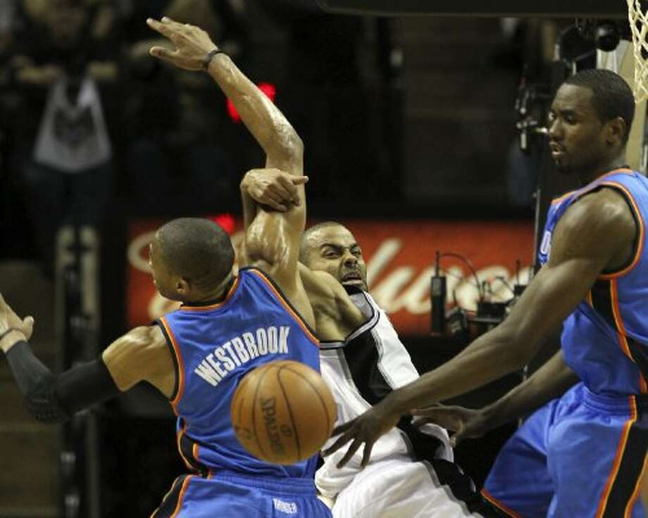 San Antonio Spurs' Tony Parker (9) passes around Oklahoma City Thunder's Russell Westbrook (0) and Oklahoma City Thunder's Serge Ibaka (9) during the first half of game one of the NBA Western Conference Finals in San Antonio, Texas on Sunday, May 27, 2012. (San Antonio Express-News)