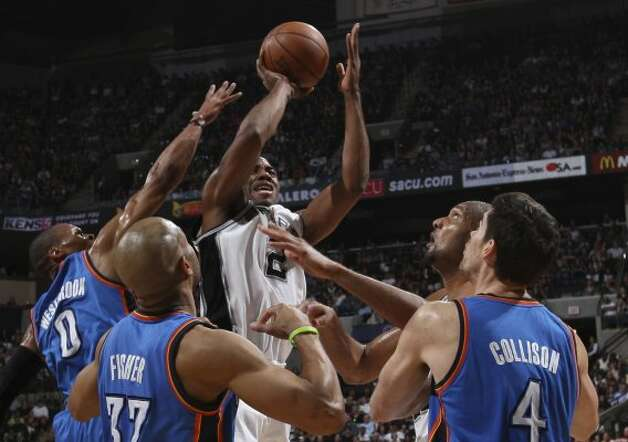 San Antonio Spurs' Kawhi Leonard (2) shoots against Oklahoma City Thunder's Russell Westbrook (0), Oklahoma City Thunder's Derek Fisher (37) and Oklahoma City Thunder's Nick Collison (4) during the first half of game one of the NBA Western Conference Finals in San Antonio, Texas, Sunday, May 27, 2012. (San Antonio Express-News)