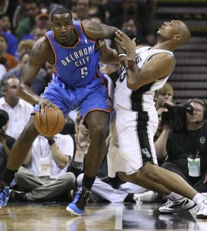 Oklahoma City Thunder's Kendrick Perkins (5) dribbles against San Antonio Spurs' Boris Diaw (33) during the first half of game one of the NBA Western Conference Finals in San Antonio, Texas, Sunday, May 27, 2012. (San Antonio Express-News)
