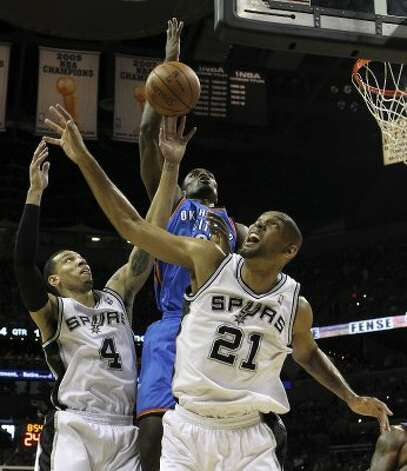 Oklahoma City Thunder's Kendrick Perkins (5) goes to the basket against San Antonio Spurs' Danny Green (4) and San Antonio Spurs' Tim Duncan (21) during the first half of game one of the NBA Western Conference Finals in San Antonio, Texas on Sunday, May 27, 2012. (San Antonio Express-News)
