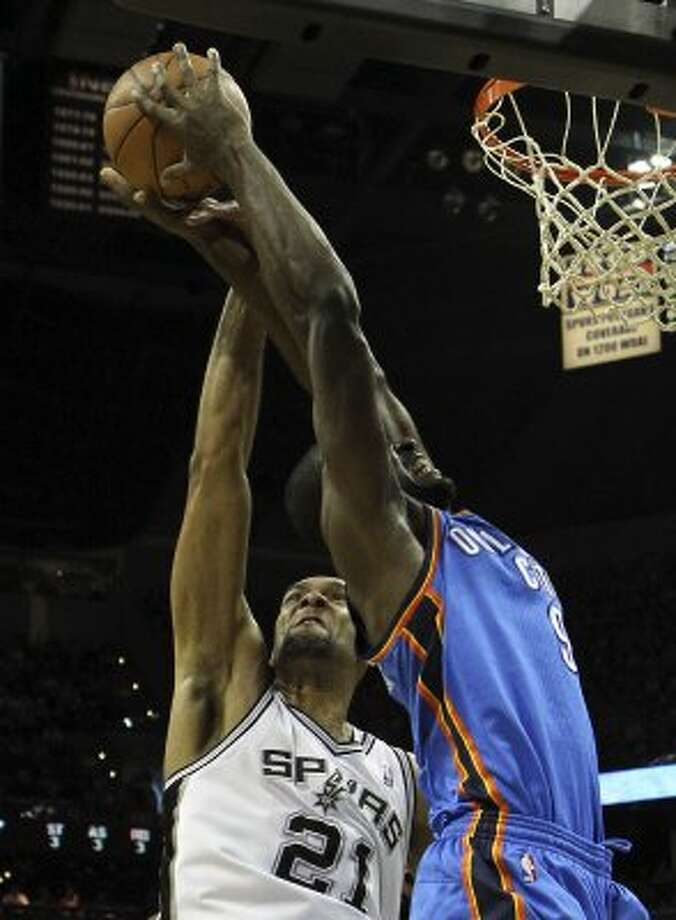San Antonio Spurs' Tim Duncan (21) gets a hand on the ball against Oklahoma City Thunder's Serge Ibaka (9) during the first half of game one of the NBA Western Conference Finals in San Antonio, Texas on Sunday, May 27, 2012. (San Antonio Express-News)