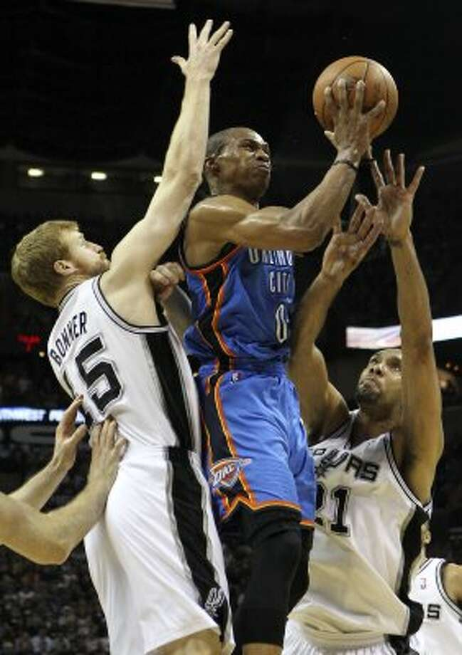 Oklahoma City Thunder's Russell Westbrook (0) splits San Antonio Spurs' Matt Bonner (15) and San Antonio Spurs' Tim Duncan (21) during the first half of game one of the NBA Western Conference Finals in San Antonio, Texas on Sunday, May 27, 2012. (San Antonio Express-News)
