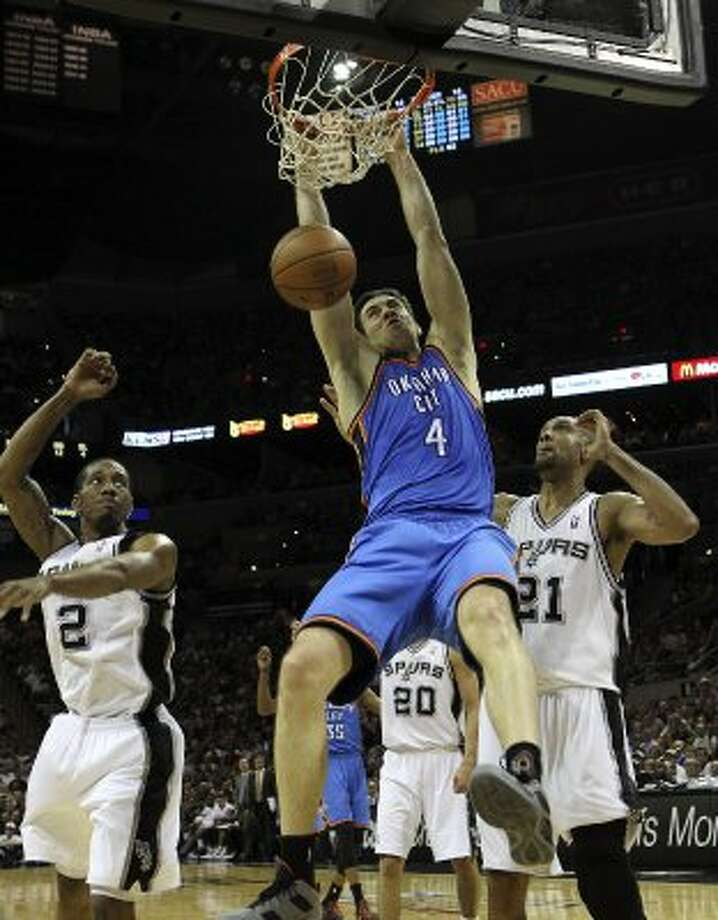 Oklahoma City Thunder's Nick Collison (4) dunks over San Antonio Spurs' Kawhi Leonard (2) and San Antonio Spurs' Tim Duncan (21) during the first half of game one of the NBA Western Conference Finals in San Antonio, Texas on Sunday, May 27, 2012. (San Antonio Express-News)