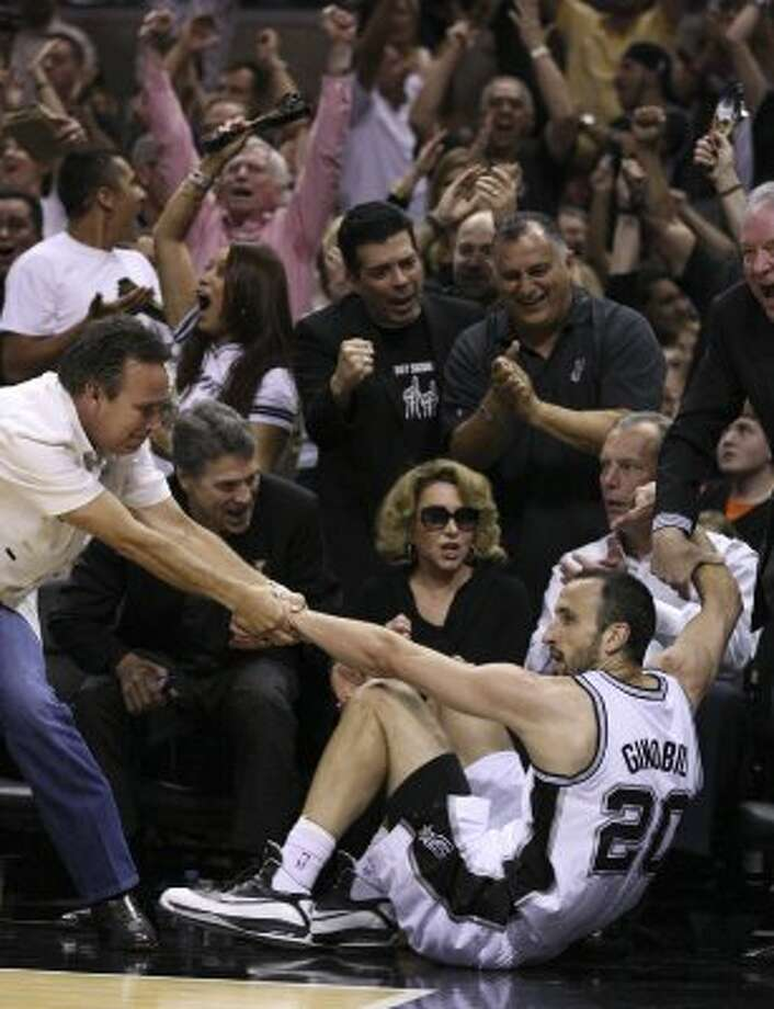 Texas Gov. Rick Perry, left, cheers as San Antonio Spurs' Manu Ginobili (20) is helped off the court after hitting a three point basket during the first half of game one of the NBA Western Conference Finals in San Antonio, Texas, Sunday, May 27, 2012. Pictured at bottom center is Julianna Holt, wife of Spurs owner Peter Holt. Seated next to Julianna Holt is Lt. Gov. David Dewhurst and at far right, helping Ginobili up,  is Peter Holt. (San Antonio Express-News)