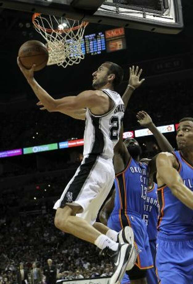 San Antonio Spurs' Manu Ginobili (20) lays the ball in against Oklahoma City Thunder's Thabo Sefolosha, right, during the second half of game one of the NBA Western Conference Finals in San Antonio, Texas on Sunday, May 27, 2012. (San Antonio Express-News)