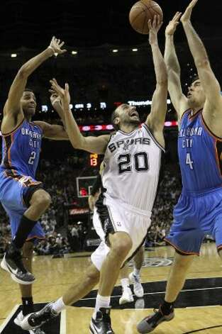 San Antonio Spurs' Manu Ginobili (20) loses control of the ball against Oklahoma City Thunder's Thabo Sefolosha (2) and Oklahoma City Thunder's Nick Collison (4) during the second half of game one of the NBA Western Conference Finals in San Antonio, Texas on Sunday, May 27, 2012. (San Antonio Express-News)
