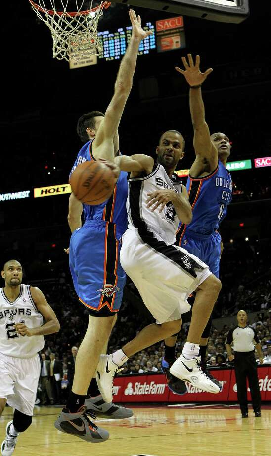 San Antonio Spurs' Tony Parker (9) passes around Oklahoma City Thunder's Nick Collison (4) and Oklahoma City Thunder's Russell Westbrook (0) during the second half of game one of the NBA Western Conference Finals in San Antonio, Texas on Sunday, May 27, 2012. Photo: Kin Man Hui, San Antonio Express-News / © 2012 San Antonio Express-News