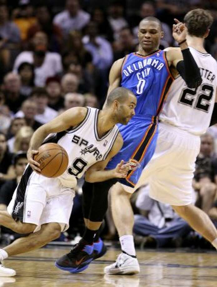 San Antonio Spurs' Tony Parker (9) drives around Oklahoma City Thunder's Russell Westbrook (0) and San Antonio Spurs' Tiago Splitter (22) during the second half of game one of the NBA Western Conference Finals in San Antonio, Texas, Sunday, May 27, 2012. (San Antonio Express-News)