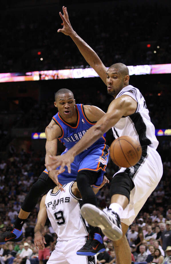 Oklahoma City Thunder's Russell Westbrook (0) passes around San Antonio Spurs' Tim Duncan (21) during the second half of game one of the NBA Western Conference Finals in San Antonio, Texas, Sunday, May 27, 2012. Photo: Edward A. Ornelas, San Antonio Express-News / © 2012 San Antonio Express-News