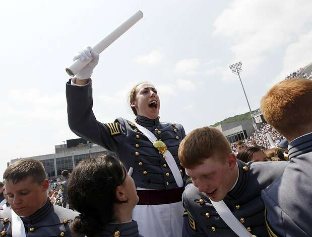 In this Saturday, May 26, 2012 photo, Kaitlyn Kelly, center, reacts after a graduation and commissioning ceremony at the U.S. Military Academy in West Point, N.Y. At West Point, the alumni gay advocacy group Knights Out was able to hold the first installment in March of what is intended to be an annual dinner in recognition of gay and lesbian graduates and cadets. Kelly was among the dozens of cadets who attended the privately sponsored dinner. The 22-year-old Chicago resident was finally able to openly introduce her civilian girlfriend at an event marking 100 days before graduation. (AP Photo/Mike Groll) Photo: Mike Groll, Associated Press