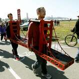 Dustin Finkle, (left) and Tim Koning, of San Francisco, took about fifthteen hours to construct a wearable replica of the Golden Gate bridge, as they walk around during the 75th anniversary celebration of the Golden Gate Bridge along Crissy Field, on Sunday May 27, 2012, in San Francisco, Ca.