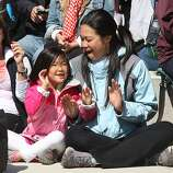 Kylie Choi (left) and her mother Camille Tsao (right) enjoy listening to singing group Chilled On at east Crissy Field in San Francisco, California, on Sunday, May 27, 2012, during the Golden Gate Bridge 75th anniversary.
