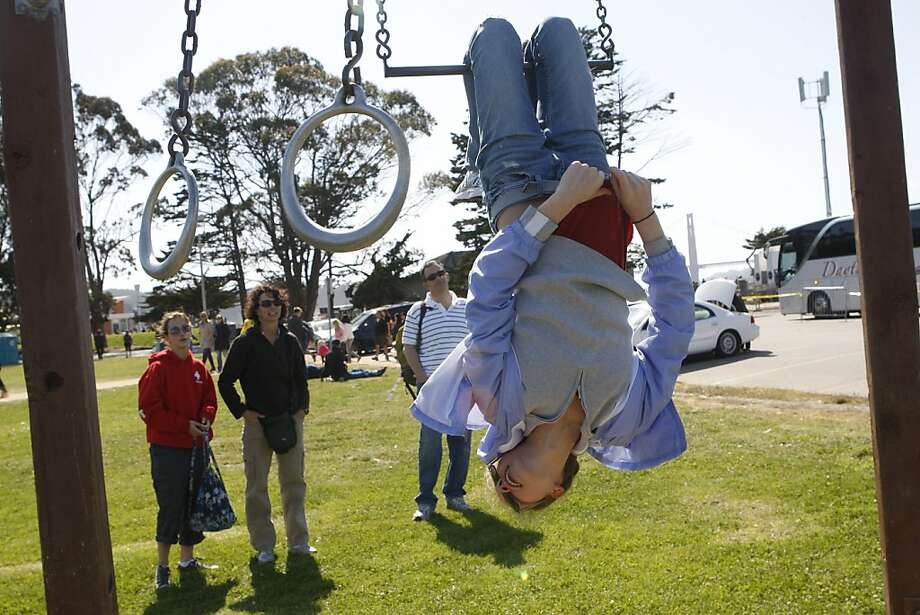 Emily Hogan, 14 years old, from San Francisco hanging upside down from a bar at east Crissy Field in San Francisco, California, on Sunday, May 27, 2012, during the Golden Gate Bridge 75th anniversary. Photo: Liz Hafalia, The Chronicle
