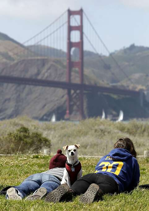Alicia Olsen (left) and Autumn Cleave, along with dog Louie, lounge along Crissy Field as boats dot the bay under the bridge. Photo: Michael Macor, The Chronicle