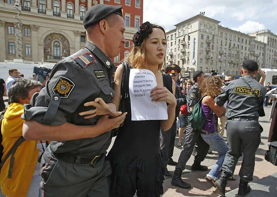 Russian police officers detain a gay rights activist  during an attempt to hold a gay pride parade in Moscow, Russia, Sunday, May 27, 2012. Russian police have detained around a dozen protesters demanding the right to hold a gay pride parade in Moscow. Activists have long petitioned the government for permission to stage such a parade, but have always been denied. A woman in center holds paper with a sign reading 'Beauty against terror and  a fascist state'. (AP Photo/Mikhail Metzel) Photo: Mikhail Metzel, Associated Press