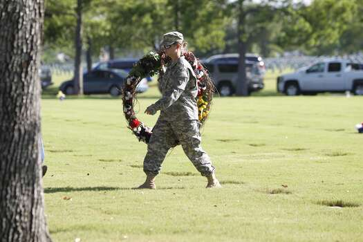 A soldier carries a wreath at the Houston national cemetery, Monday, May 28, 2012. Photo: Karen Warren, Houston Chronicle
