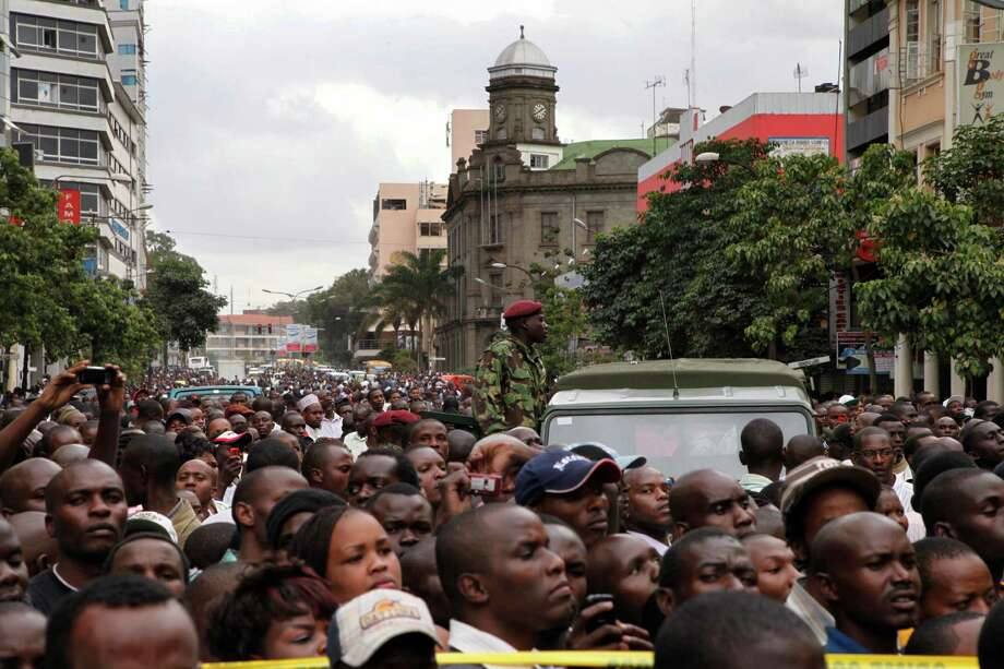 Crowds jam the street after an explosion on a busy road in downtown Nairobi, Kenya, Monday, May 28, 2012.  An explosion ripped through a building full of small shops in downtown Nairobi on Monday, wounding at least 16 people, the police commissioner said. He could not immediately say what caused the early morning blast that sent smoke billowing out of the building and over the city.  (AP Photo/Sayyid Azim) Photo: Sayyid Azim, Associated Press / AP