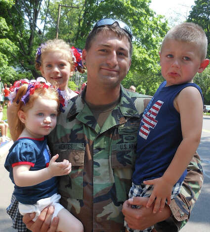 Army Specialist Steve Mentes, 82nd Airborne, with nieces Ireland and Morgan and son Colton along the Fairfield Memorial Day parade route Monday. Photo: Mike Lauterborn / Fairfield Citizen contributed