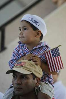 Joel Diaz Jr, 3, sits on his dad, Joel Diaz's shoulders as they listen to a speaker during Memorial Day ceremonies at the Houston national cemetery, Monday may 28,2012 (Karen Warren/Houston Chronicle)