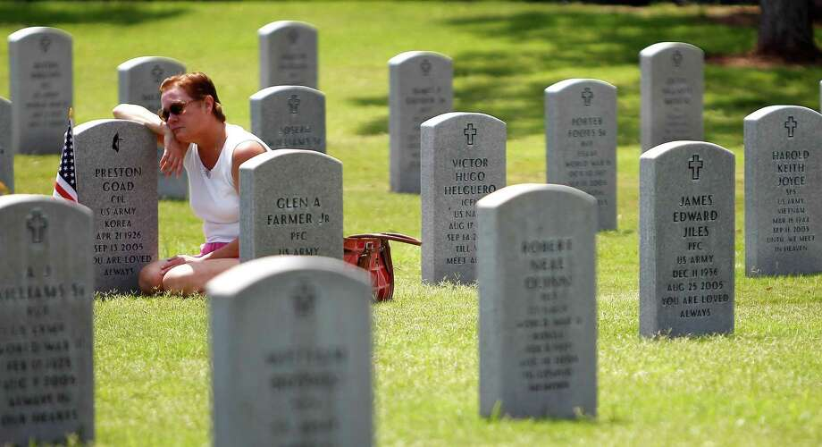 At the Houston National Cemetery, Debbie Hinojosa sits at the grave of her father, Preston Goad, who died in September 2005. Photo: Karen Warren, Houston Chronicle / © 2012  Houston Chronicle