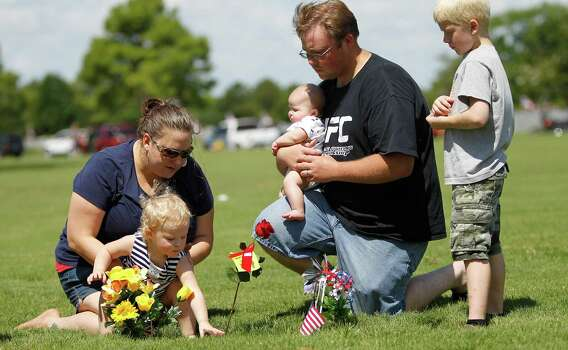 Lindsey Lewis, 2, touches the grave of her grandfather, Troy Lewis Jr. (a Navy WWII vet) with her mother, Jennifer Lewis and her dad, Steven Lewis, right, holding 4-month old Logan Lewis along with cousin, Tyler Tyburczyk, 9, far right after the Memorial Day ceremony at the Houston National Cemetery, Monday, May 28, 2012, in Houston. Photo: Karen Warren, Houston Chronicle / © 2012  Houston Chronicle