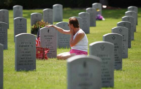 """Debbie Hinojosa sits at the grave of her father, Preston Goad, an army veteran, who died in September 2005 on  Memorial Day at the Houston National Cemetery, Monday, May 28, 2012, in Houston. """"I miss my daddy..he was my angel"""" said Hinojosa. Photo: Karen Warren, Houston Chronicle / © 2012  Houston Chronicle"""