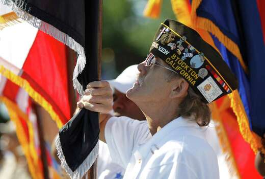 Rosco Perry a verteran of the Marine Corps holds the POW flag as he stands with members of the US Vets group during the Memorial Day ceremony at the Houston National Cemetery, Monday, May 28, 2012, in Houston. Photo: Karen Warren, Houston Chronicle / © 2012  Houston Chronicle