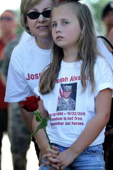 Maddison Bass, 8, holds a flower while wearing a t-shirt with her cousin, Joseph Alvarez's photo on it as she talks to Mary Williams during the Memorial Day ceremony at the Houston National Cemetery, Monday, May 28, 2012, in Houston. Alvarez was in the National Guard and died in October 2011. Photo: Karen Warren, Houston Chronicle / © 2012  Houston Chronicle