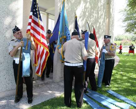 Members of the Texas Lone Star Korean War Veterans roll up their flags after they participated in the Memorial Day ceremony at the Houston National Cemetery, Monday, May 28, 2012, in Houston. Photo: Karen Warren, Houston Chronicle / © 2012  Houston Chronicle