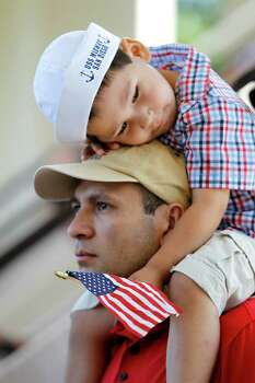 Joel Diaz Jr., 3-years-old, sits on the shoulders of his dad, Joal Diaz, as they listen to a speaker during the Memorial Day ceremony at the Houston National Cemetery, Monday, May 28, 2012, in Houston. Photo: Karen Warren, Houston Chronicle / © 2012  Houston Chronicle