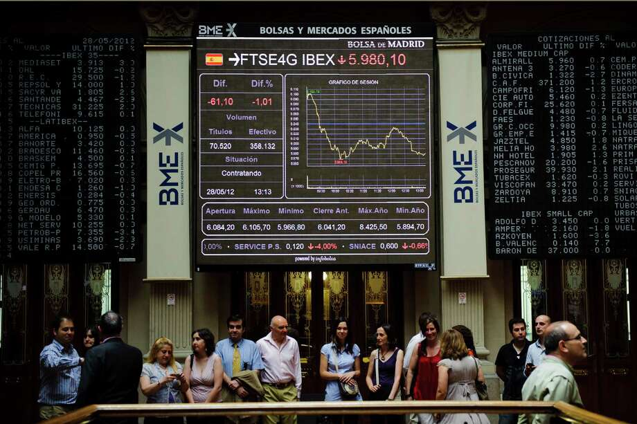 Visitors pose for pictures under the main display at the Stock Exchange in Madrid, Monday, May 28, 2012. Conservative Spanish Prime Minister Mariano Rajoy was adamant Monday that Spain's bank sector would not need an international rescue as concern over the bailout fund for nationalized lender Bankia sent that bank's stock price plummeting while Spain's borrowing costs soared. (AP Photo/Daniel Ochoa de Olza) Photo: Daniel Ochoa De Olza / AP