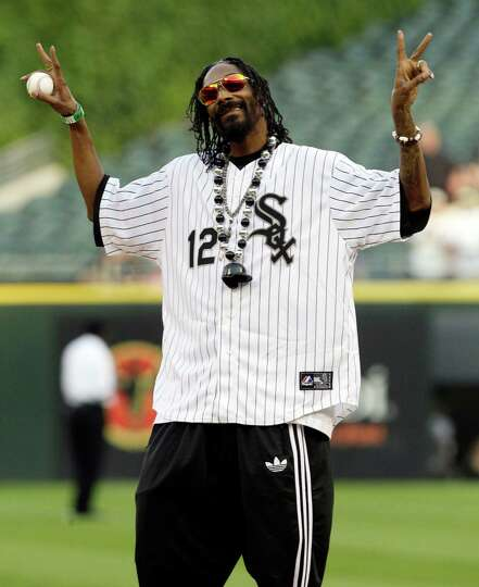 Rapper Snoop Dogg gestures before throwing out a ceremonial first pitch before a baseball game betwe