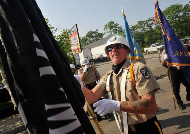 American Legion member Allen Keeler unfurls the POW/MIA flag before the start of the Danbury Memorial Day Parade on Monday, May 28, 2012. Photo: Jason Rearick / The News-Times