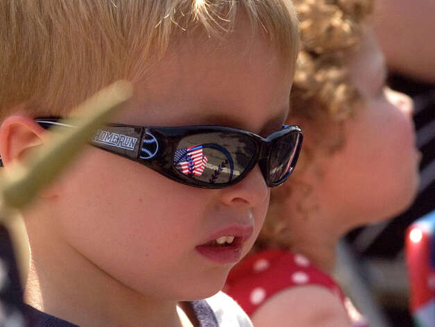 Jacob Topham, 4, watches the parade go by as the American flag he is holding is reflected in his sunglasses during the Danbury Memorial Day Parade on Monday, May 28, 2012. Photo: Jason Rearick / The News-Times