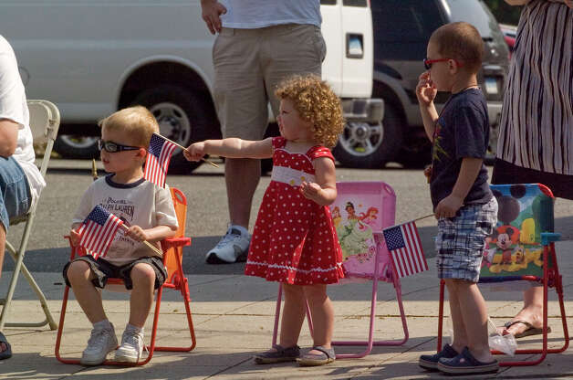 From left, Jacob Topham, 4, Alexa Topa, 2, and Kyler Topa, 3, watch the Danbury Memorial Day Parade go down Main Street on Monday, May 28, 2012. Photo: Jason Rearick / The News-Times