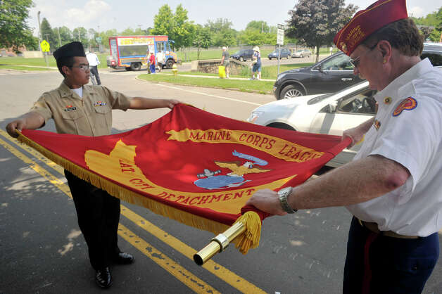 Kenny Thach, left, and Bill Moser put away the Marine Corps League flag after the Rose Arbor ceremony at Rogers Park in Danbury on Monday, May 28, 2012. Photo: Jason Rearick / The News-Times