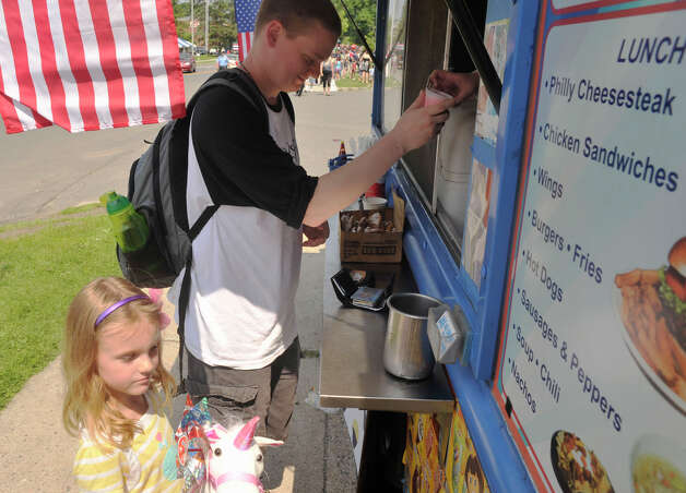 Chris Morton and his daughter, Lily, cool off by getting ice cream from J&E Ice Cream and More during the Danbury Memorial Day Parade on Monday, May 28, 2012. Photo: Jason Rearick / The News-Times