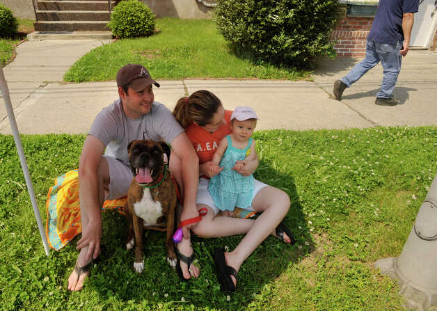 Newtown residents, Jeff Stenhouse, Dora, their 8-month-old daughter McKenzie and their dog Daisy take in the Danbury Memorial Day Parade on Monday, May 28, 2012. Photo: Jason Rearick / The News-Times
