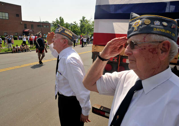 Representing the Catholic War Veterans Jim Purcell, left, and Joe DeGuilio salute as the Danbury Memorial Day Parade goes down Main Street on Monday, May 28, 2012. Photo: Jason Rearick / The News-Times