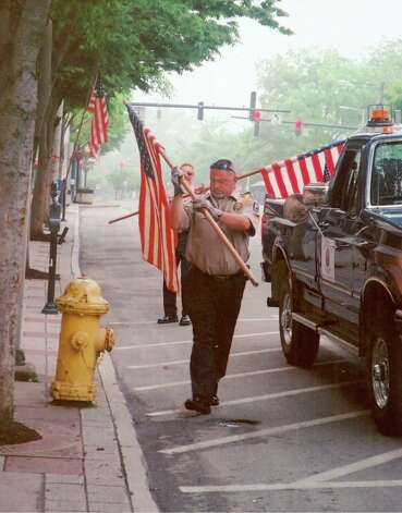 American Legion color guard member Tom Hill installs American flags along Main Street in Danbury in preparation for the Danbury Memorial Day Parade on Monday, May 28, 2012. Photo: Contributed Photo Connie Halleck, Contributed Photo / The News-Times Contributed