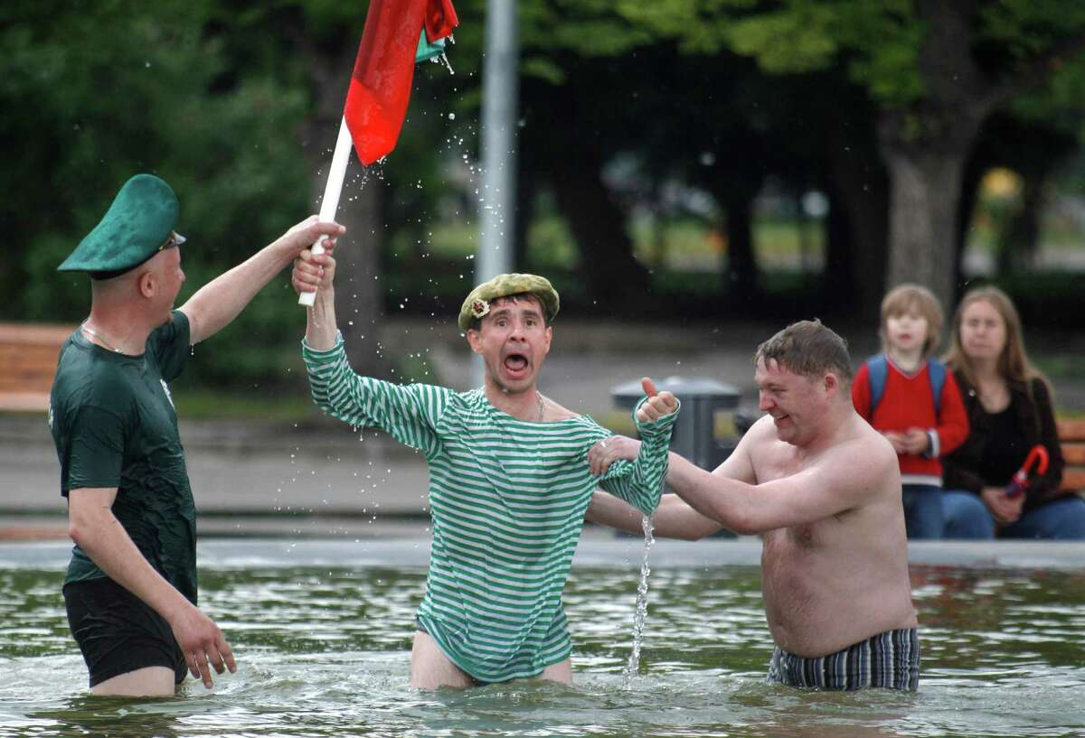 Former Russian border guards react in a fountain in Moscow's Gorky Park, Russia, Monday, May 28, 2012, as they celebrate border guards day.