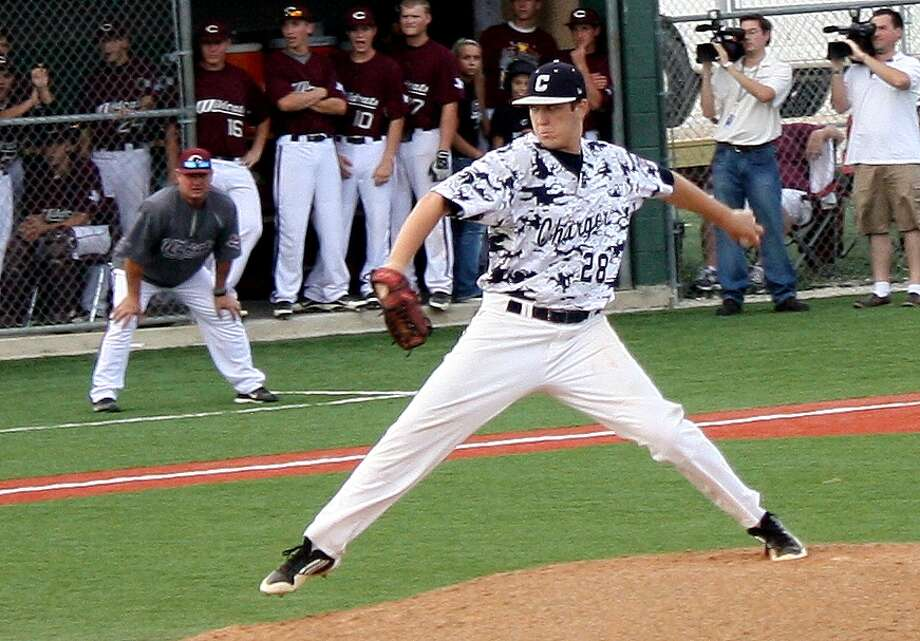 Boerne Champion senior pitcher Bryce Dorn delivers a strike as Calallen Coach Steve Chapman and his top-ranked Wildcats watch from their dugout. Dorn went the distance for the win as the Chargers upset Calallen 4-3 and advanced to the Class 4A, Region IV finals against Lake Travis. Photo: Picasa, Mike Reeder / For The Northwest Weekly