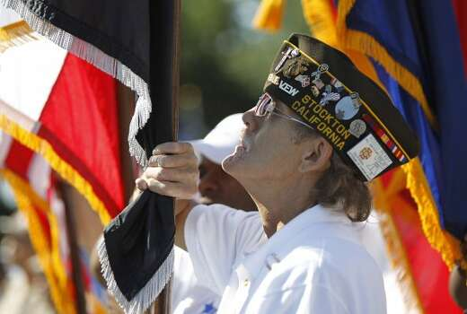 Rosco Perry, a verteran of the Marine Corps, holds the POW flag as he stands with members during the Memorial Day ceremony at the Houston National Cemetery, Monday, May 28, 2012, in Houston. ( Karen Warren / Houston Chronicle )  (© 2012  Houston Chronicle)