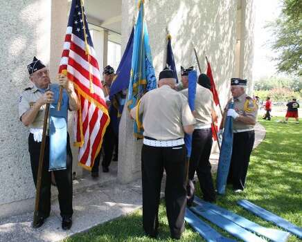 Members of the Texas Lone Star Korean War Veterans roll up their flags after they participated in the Memorial Day ceremony at the Houston National Cemetery, Monday, May 28, 2012, in Houston. ( Karen Warren / Houston Chronicle )  (© 2012  Houston Chronicle)