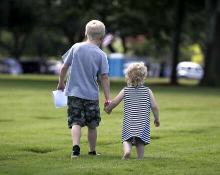 Tyler Tyburczyk, 9, holds the hand of his cousin, Lindsey Lewis, 2, as they walk around the grave sites during the Memorial Day ceremony at the Houston National Cemetery, Monday, May 28, 2012, in Houston. ( Karen Warren / Houston Chronicle ) May 28, 2012  (© 2012  Houston Chronicle)