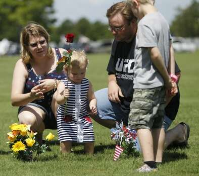Lindsey Lewis, 2, places a rose on the grave of her grandfather, Troy Lewis Jr. (a Navy WWII vet) with her auntSandra Lott-Tyburczyk, left, and her dad, Steven Lewis, right and cousin, Tyler Tyburczyk, 9, after the Memorial Day ceremony at the Houston National Cemetery, Monday, May 28, 2012, in Houston. ( Karen Warren / Houston Chronicle ) (© 2012  Houston Chronicle)