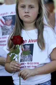 Maddison Bass, 8, holds a flower while wearing a t-shirt with her cousin, Joseph Alvarez's photo on it as she talks to Mary Williams during the Memorial Day ceremony at the Houston National Cemetery, Monday, May 28, 2012, in Houston. Alvarez was in the National Guard and died in October 2011. ( Karen Warren / Houston Chronicle )  (© 2012  Houston Chronicle)