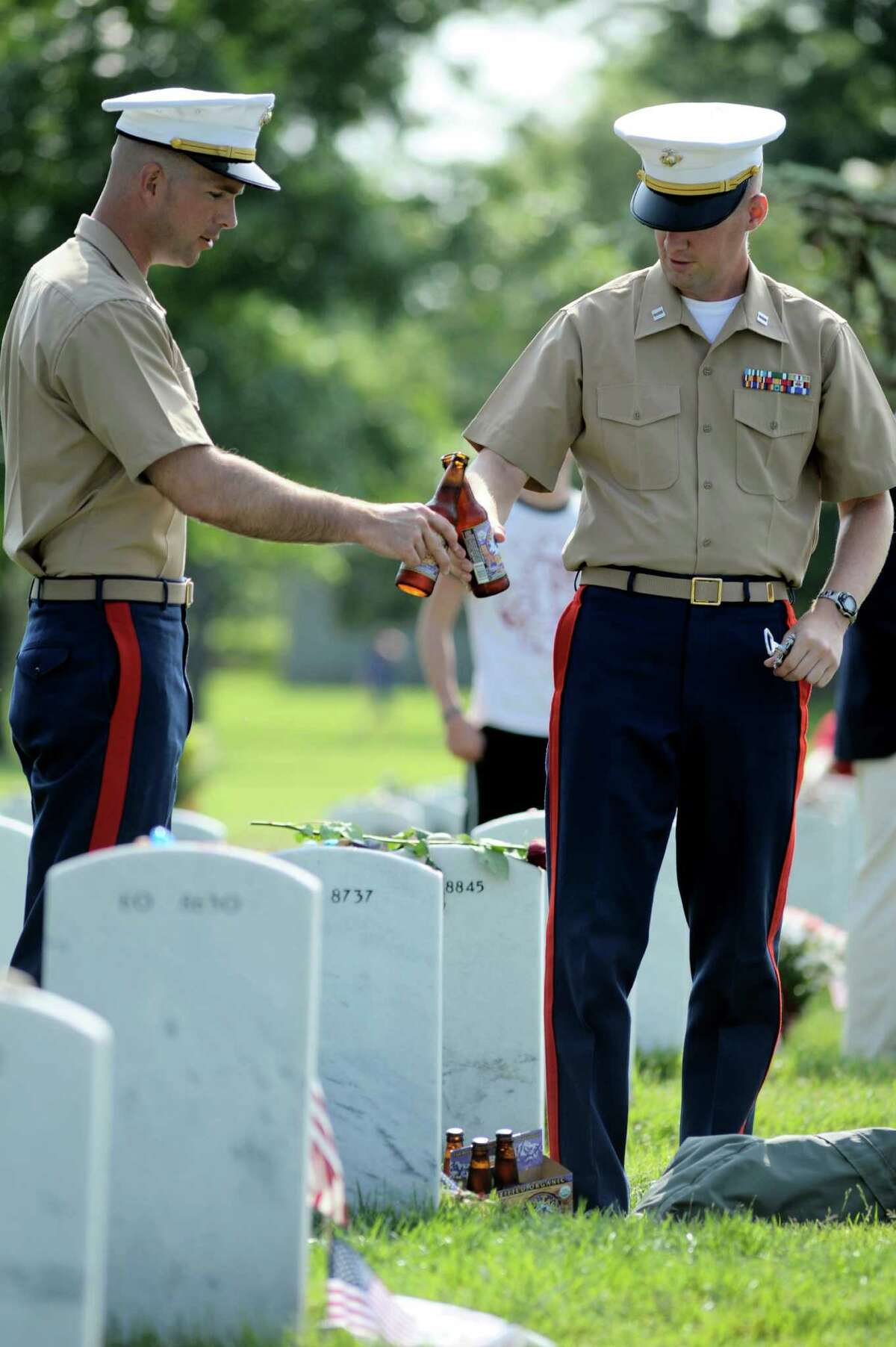 Marine Captains Brady Bustin, of Des Moines, Iowa, left, and Sean Wills, of Herndon, Va., toast fallen Marine 1st Lt. Nicholas Madrazo, in Section 60 at Arlington National Cemetery, in Arlington, Va., Monday, May 28, 2012. Madrazo, of Bothell, Wash., was killed Sept. 9, 2008, by a roadside bomb in Parwan province, Afghanistan
